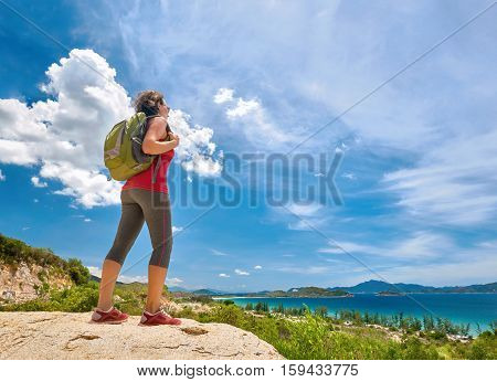 Tourist with backpack standing on a rock on clear sky background looking at beautiful landscape motivation and inspiration.