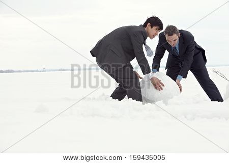 Two elegant businessmen making large snowball in field