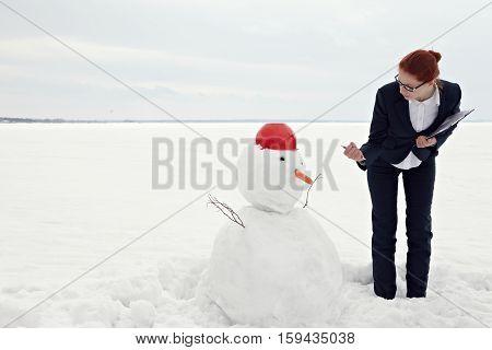 Businesswoman threatening with her fist to snowman