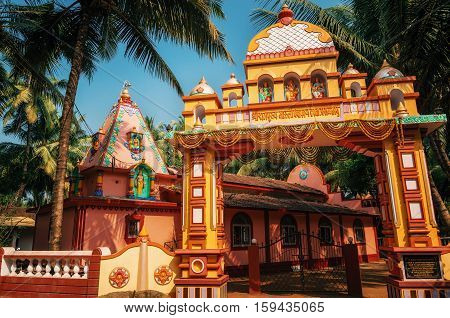 Vivid colorful Hindu Temple at Morjim amidst a coconut grove North Goa India.