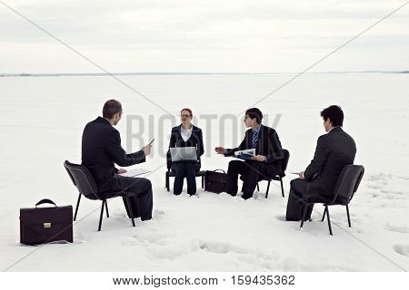 Business people having a discussion on snowy field