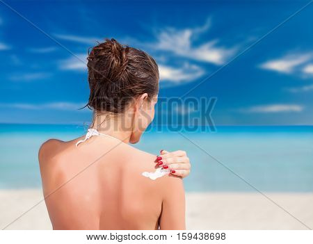A smiling woman is applying sunblock on sandy beach near blue sea