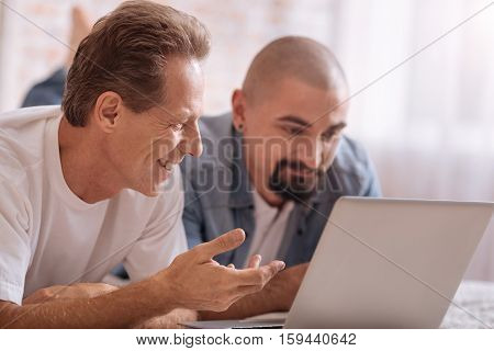 Surfing the Internet together. Cheerful smiling involved friends lying on the bed in front of the laptop while expressing interest and sharing opinions