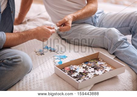 Joyful game. Numerous colorful small puzzle pieces lying in the box and on the bed while being the part of the game of two men