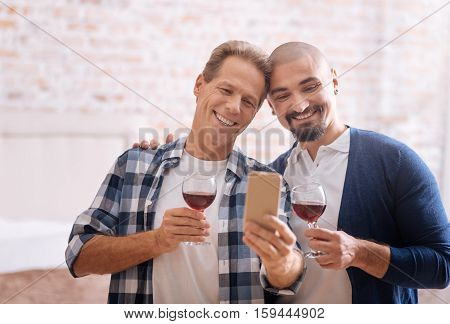 We enjoying our romantic moment together. Delighted cheerful gay couple standing in the bedroom and drinking wine while hugging each other and taking selfie