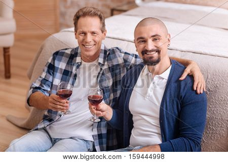 We love each other. Cheerful happy delighted non-traditional couple sitting in the bedroom and drinking wine while expressing love and care and hugging each other