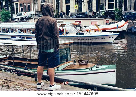 Amsterdam Netherlands - August 2 2016: Man looking at the canal in Amsterdam city center. It is one of the most romantic and beautiful cities in Europe. Amsterdam is also a city of tolerance and diversity.