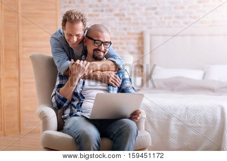 I enjoy hugging you. Delighted positive cheerful homosexual man standing in the bedroom and hugging his love while expressing happiness and his partner using the laptop