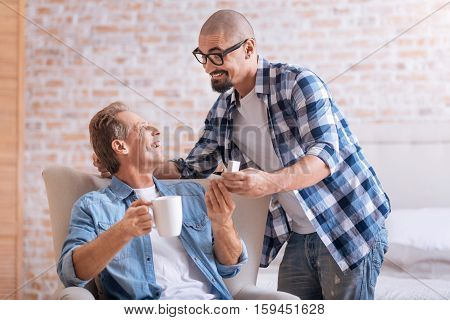 I want to be with you forever. Cheerful positive young homosexual man standing in the bedroom and hugging his love while making the proposal and his partner expressing happiness