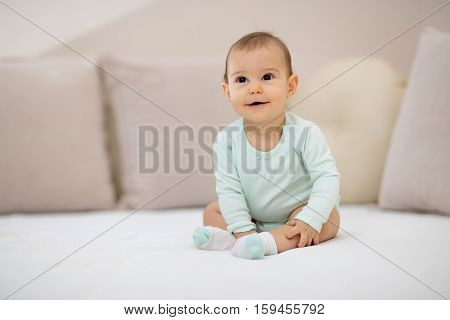 Such a happy little baby girl. Beautiful cute soft baby girl sitting on bed