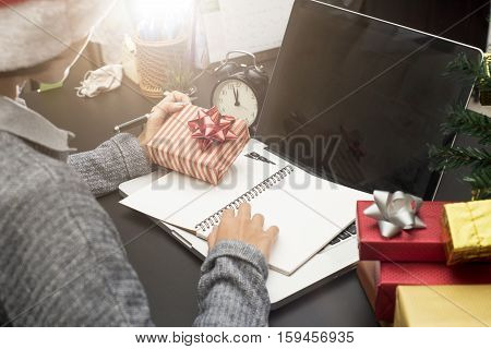 business woman hand holding gift box working on desk office concept office christmas and happy new year.