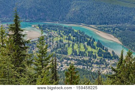 An elevated of view of a golf course Revelstoke townsite and Columbia River. Revelstoke British Columbia Canada