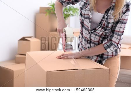 House moving concept. Closeup of woman packing cardboard box