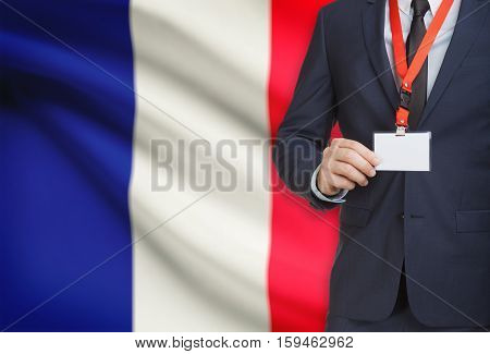 Businessman Holding Name Card Badge On A Lanyard With A National Flag On Background - France