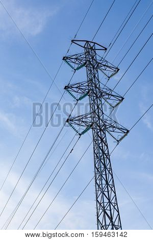High voltage pole against blue sky background