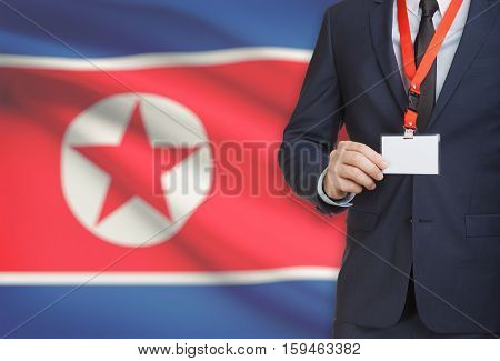 Businessman Holding Name Card Badge On A Lanyard With A National Flag On Background - North Korea