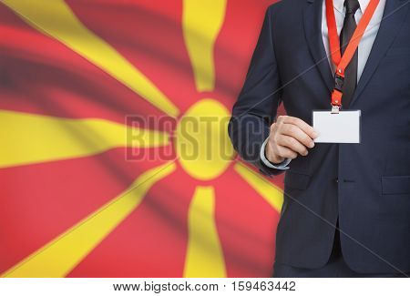 Businessman Holding Name Card Badge On A Lanyard With A National Flag On Background - Macedonia
