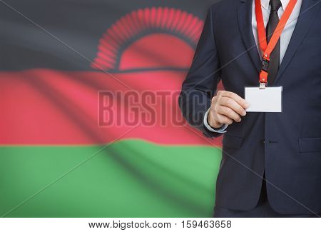 Businessman Holding Name Card Badge On A Lanyard With A National Flag On Background - Malawi
