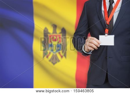 Businessman Holding Name Card Badge On A Lanyard With A National Flag On Background - Moldova