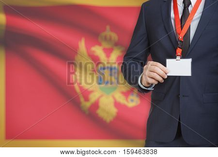 Businessman Holding Name Card Badge On A Lanyard With A National Flag On Background - Montenegro