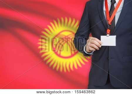 Businessman Holding Name Card Badge On A Lanyard With A National Flag On Background - Kyrgyzstan