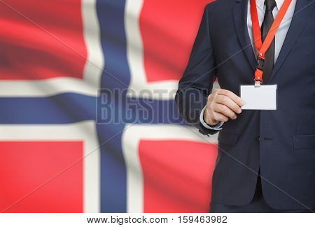 Businessman Holding Name Card Badge On A Lanyard With A National Flag On Background - Norway