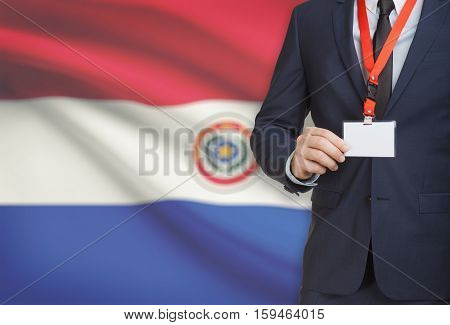 Businessman Holding Name Card Badge On A Lanyard With A National Flag On Background - Paraguay