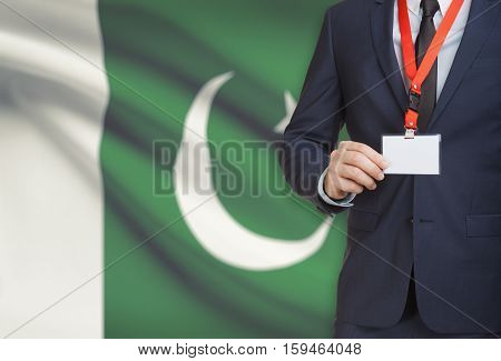 Businessman Holding Name Card Badge On A Lanyard With A National Flag On Background - Pakistan