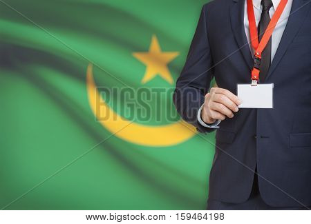 Businessman Holding Name Card Badge On A Lanyard With A National Flag On Background - Mauritania