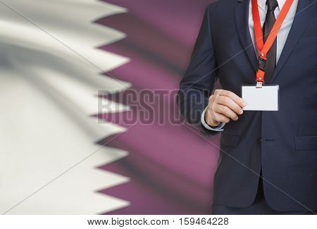 Businessman Holding Name Card Badge On A Lanyard With A National Flag On Background - Qatar