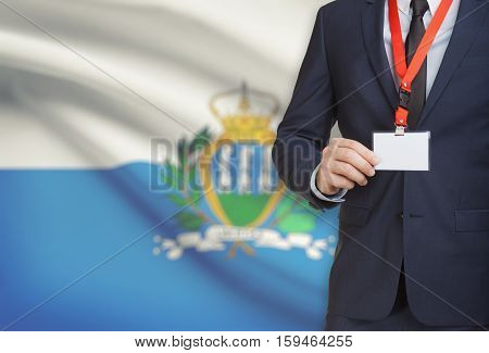 Businessman Holding Name Card Badge On A Lanyard With A National Flag On Background - San Marino