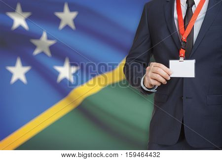 Businessman Holding Name Card Badge On A Lanyard With A National Flag On Background - Solomon Island