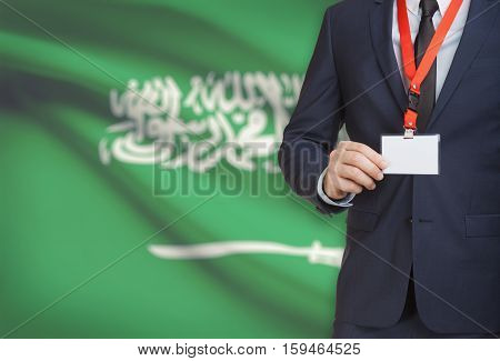 Businessman Holding Name Card Badge On A Lanyard With A National Flag On Background - Saudi Arabia