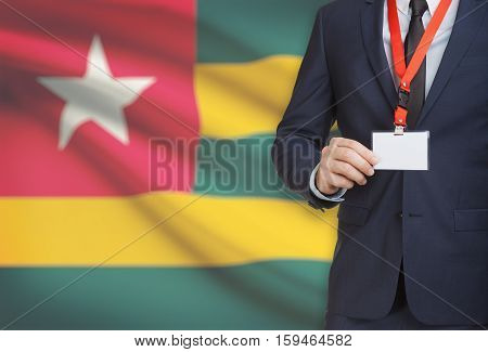 Businessman Holding Name Card Badge On A Lanyard With A National Flag On Background - Togo