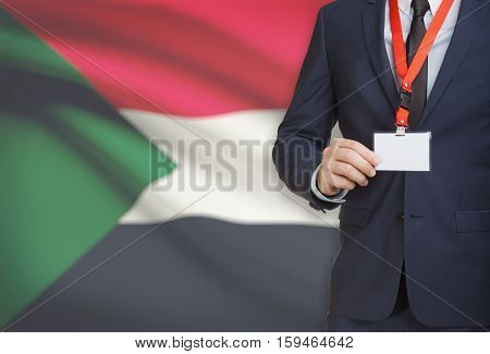 Businessman Holding Name Card Badge On A Lanyard With A National Flag On Background - Sudan