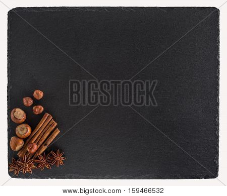 Cinnamon hazelnutand star anise on a black slate board. Isolated on white background. Top view.