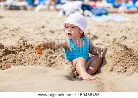 Little child girl in blue swimsuit is playing on the beach near blue sea