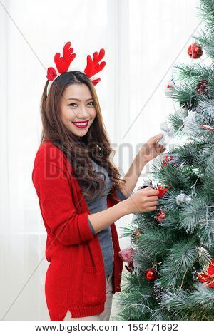Happy young asian woman standing near christmas tree at home celebrating New Year