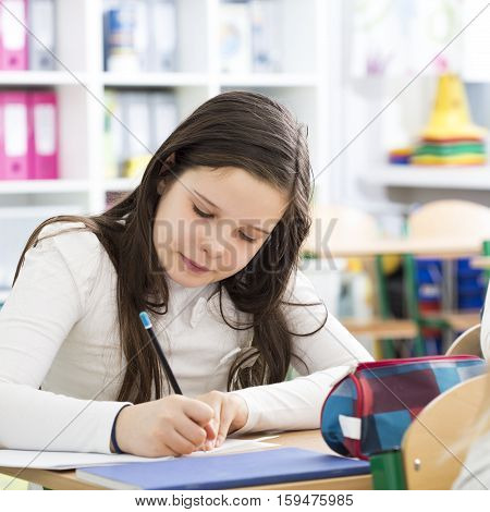 Young girl writing an essay during lesson in primary school