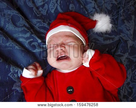 Unhappy Santa little baby crying on blue background