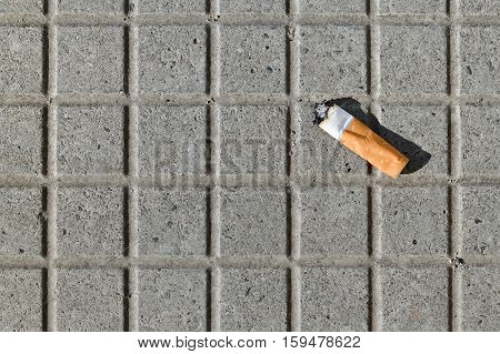 Closeup of a cigarette butt thrown on the pavement