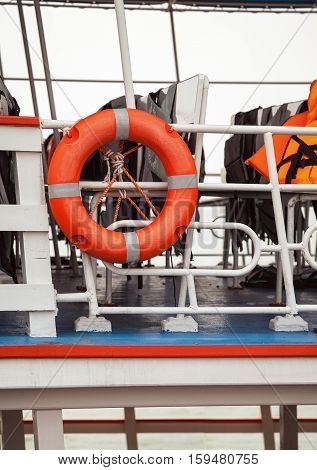 Lifebuoy and life jackets on a ferry deck close-up. Rescue equipment on a ship: buoy and vests for emergencies