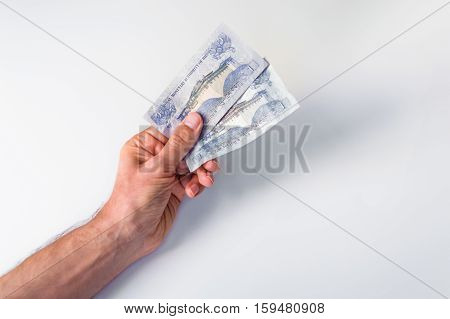 Man Holding Two Bhutanese Ngultrum Banknotes In His Hand