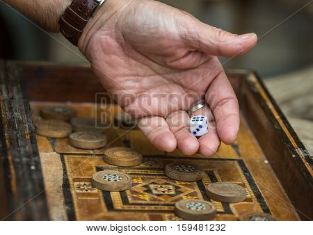 Game the antique backgammon. Man throws dice.