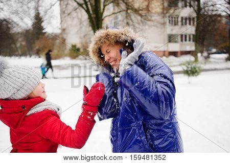 Woman turns aside from the snowballs flying to her. Daughter fires at her snowballs. Woman has exposed hands forward and cheerfully laughs. All ground is completely covered with fluffy snow.