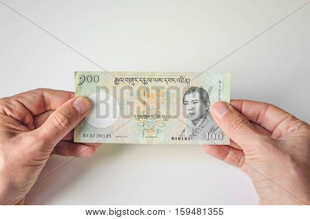 Man Holding Hundred Bhutanese Ngultrum Banknote In His Hands