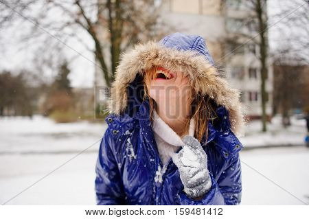 Laughing young woman after fight by snowballs. The woman's face is half hidden by a hood. A coat and gloves in snow wet hair. The woman shakes out snow from under a collar and laughs from pleasure.