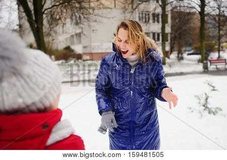Blithe young woman after fight by snowballs. The woman has wet hair and a down-padded coat in snow. But on her face delight. Nearby there is her little daughter. All ground is covered with snow. poster