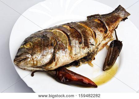 Cooked fish sea bream fish with lemon, parsley,garlic.