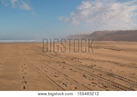 Sand of the beach with many trails and foot prints. Atlantic ocean with small waves. Cloudy sky. Silhouette of city Sidi Ifni in Morocco in a mist.